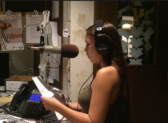 Sam speaks into a large mic, reading from a piece of paper. She is wearing headphones.