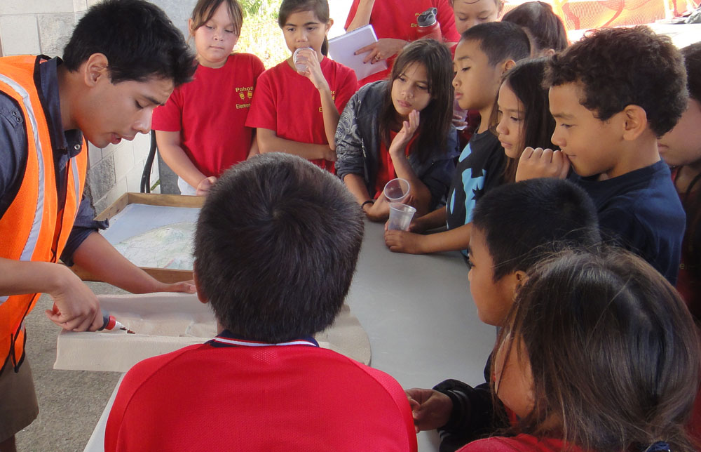 A dozen schoolchildren gather around a table where a male instructor is demonstrating flowing lava by pouring a gooey liquid into a mold.