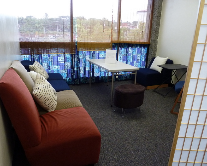 Lactation room with cozy chairs, shaded windows, a table and privacy screening.