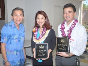 Anne Chung and Warren Kawano stand holding awards, Robert Yamane stands with them.