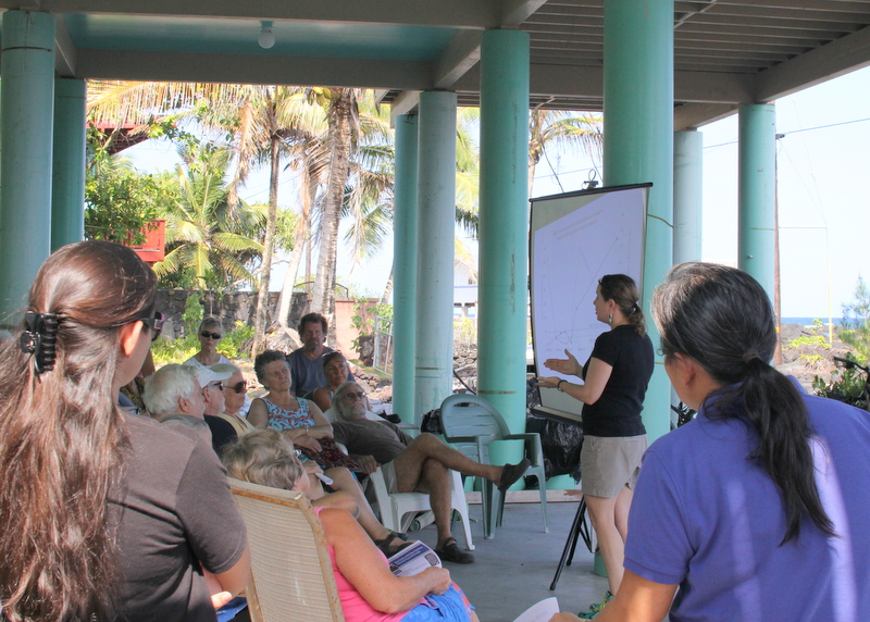 Group of residents gather on large lanai to listen to researcher speak.