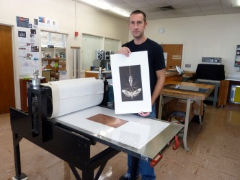 Jon Geobel stands next to printing press in his studio, holding up a print of the moth and pendulum.