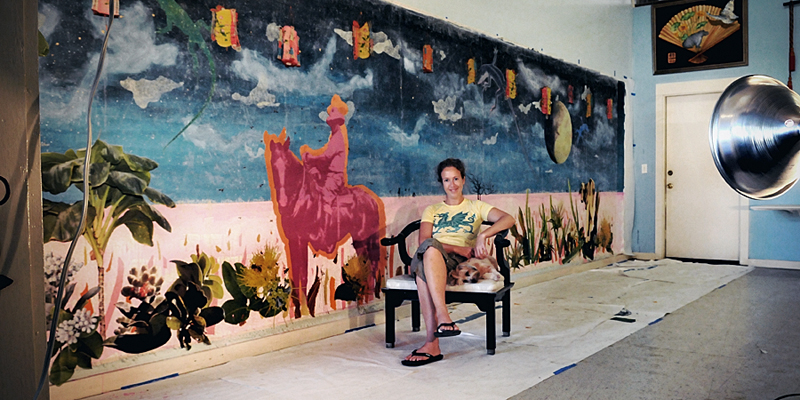 Margo Ray in her studio. Large mural on wall behind her with sky, cowboy and flora.