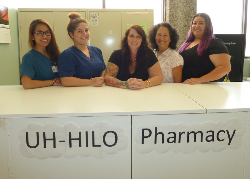 Five female staffers stand behind counter and pose for photo. Sign on face of counter: UH HILO Pharmacy.