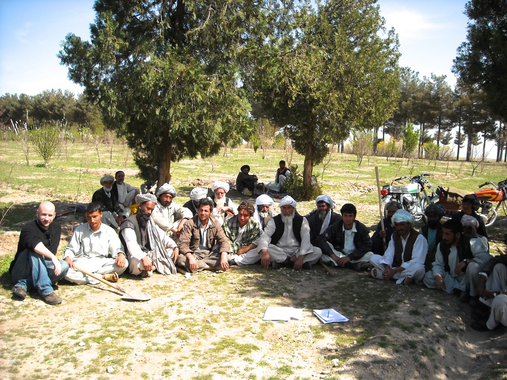 Hourihan  sits on ground with group of Afghan men in orchard.