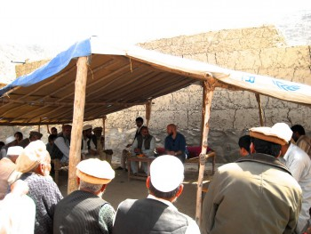 Erected tent with group of men seated inside.