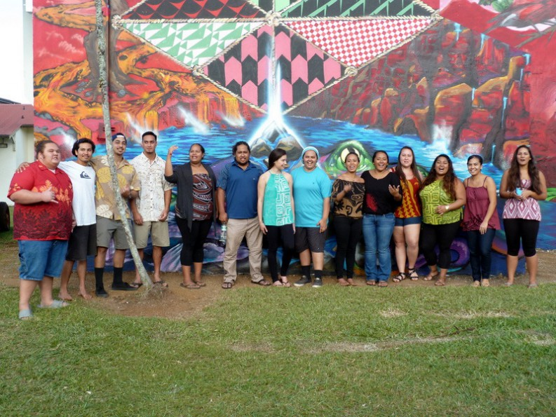A group of students stand in from of the Mele Mural, a colorful motif of Hawaiian themes.
