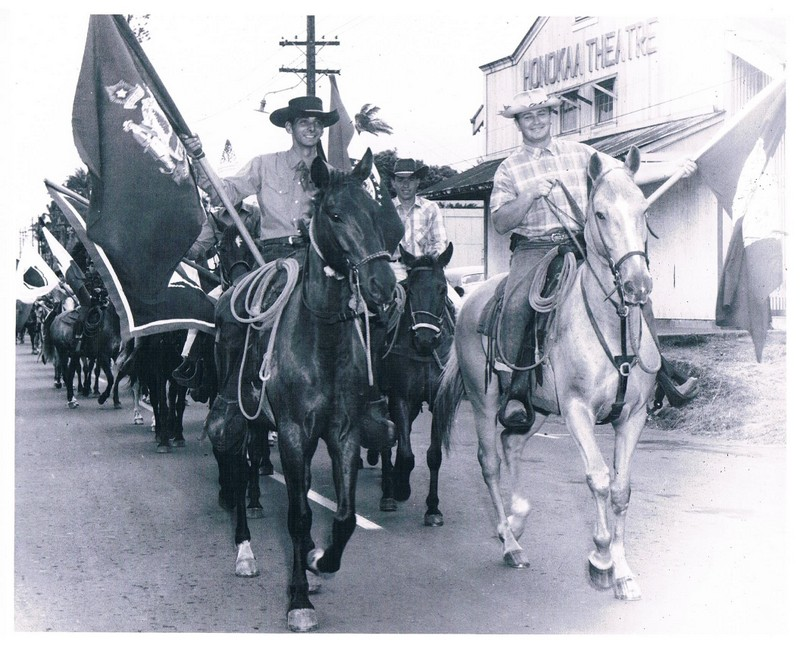 Cowboys in parade on horseback holding flags, walking down main street in Honokaa. The People's Theater can be seen in the background.