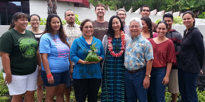 Group of 13 standing. Roberta Uno has a lei on; to her right is Keiki, director of the college, and to her left is Larry Kimura.