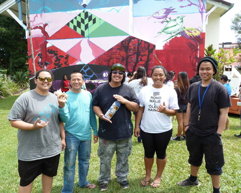 Group of painters stand in front of the mural. Mural shows images of volcano, forest birds, graphic of Maunakea, covering end wall of residence hall. IN the background are students working on the mural.