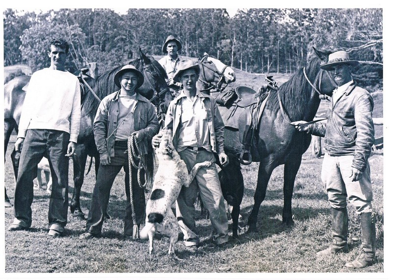 Old photo of cowboys with their saddled horses and dog.