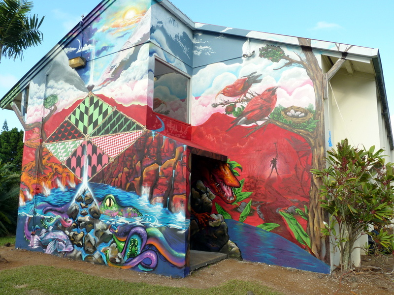 The mural is on a high wall on a residence hall and depicts colorful Hawaiian images of mountains, ocean, lava, birds, and plants.