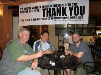 Three men seated at table in cafe. Large sign above with words: TO THOSE WHO EXTENDED THEIR AID TO THE PEOPLE OF LEYTE... THANK YOU YOU MADE A BIG DIFFERENCE IN REBUILDING OUR LIVES.