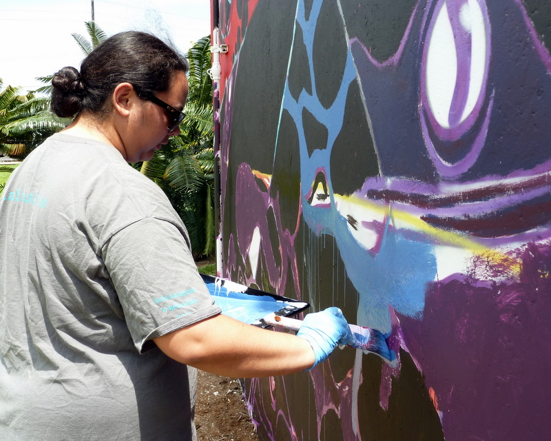 Ulu Ornellas holds a brush in right hand, painting the mural at right with a blue color.