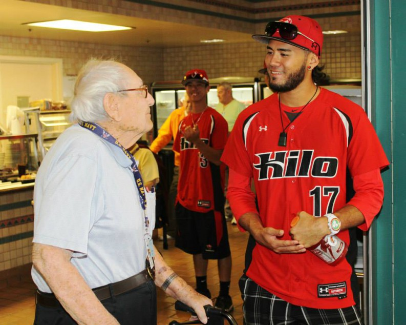 Baseball player in uniform chats with veteran.