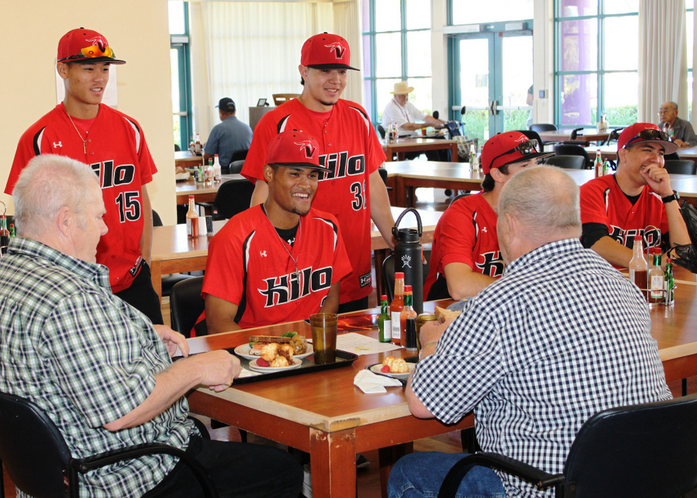 Baseball players in red uniforms visit with veterans over lunch.
