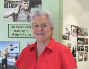 Momi Naughton standing in the Heritage Center with a display in the background. She has on a red shirt.