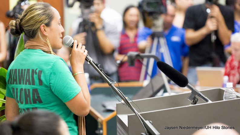 "A woman in green t-shirt with words ""Hawaii Aloha"" at podium."