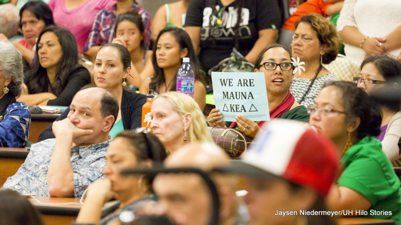 "Member of audience holds sign, ""We are Mauna Kea."" Matt Platz to left."