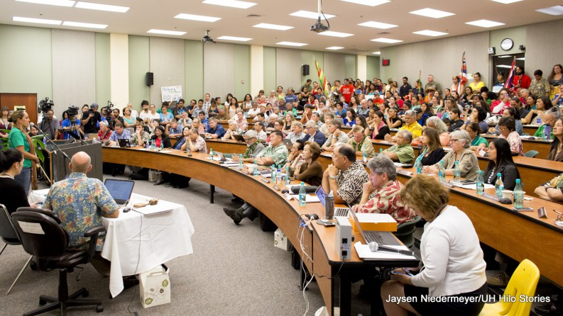 Shot of full venue. Tiered lecture hall. Filled to capacity.