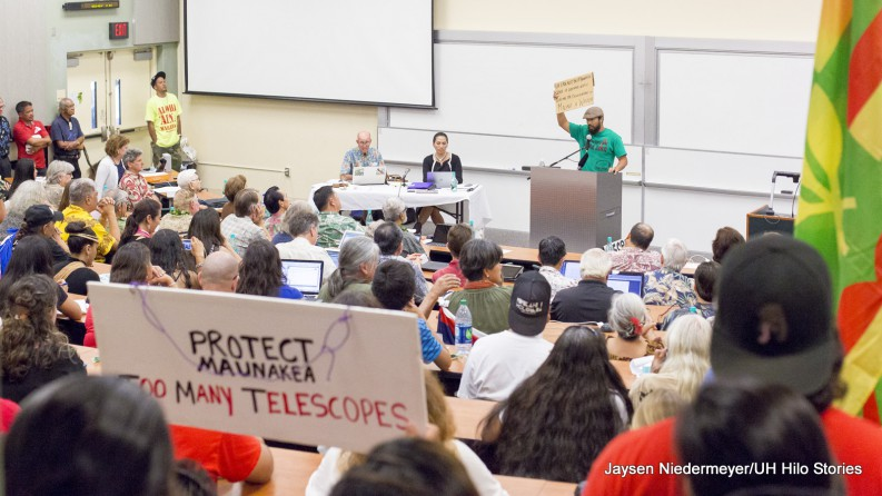 "La'akea Caravalho at podium, holds sign ver head' In the foreground is a sign, ""Protect Maunakea, too many telescopes."""