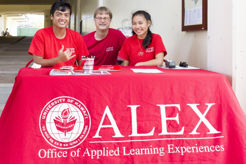Tom DeWitt (center) with two students at the sign-in table for the 2015 Applied Learning Summit. Banner reads: ALEX Office of Applied Learning. With the red University of Hawaii seal.