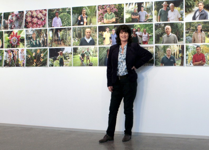 Artist stands in front of exhibit, which included photos hanging on the wall of people and plants. Courtesy photo.