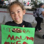 Girl with sign about Maunakea.