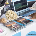 Coral, shells, pamphlets, microscope, and a laptop at the UH Hilo marine science display table.