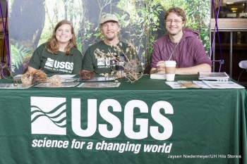 Three students sit at the U.S. Geological Survey booth. Banner: USGS science for a changing world