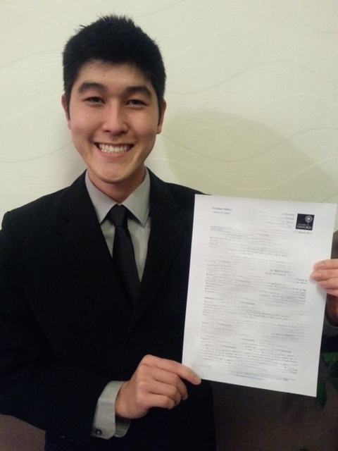 Evan Matsuyama holds up his acceptance letter from Oxford. He's wearing a suit and tie.