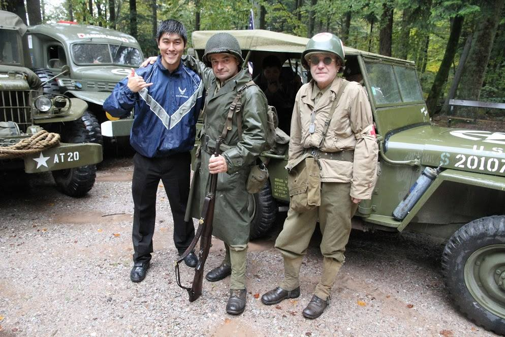 Evan Matsuyama in the field with two men in period military uniforms, jeeps in background. One man holds rifle.