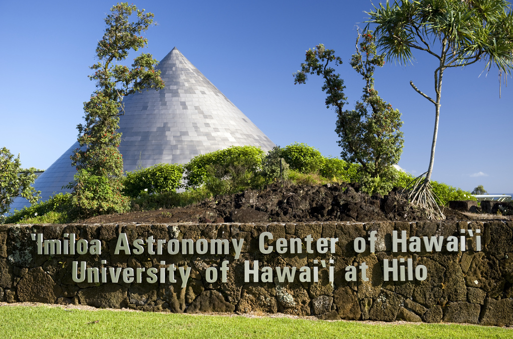 Imiloa Astronomy Center. Large silver cone roof in background. In foreground on lava wall, signage: Imiloa Astronomy Center of Hawaii, University of Hawaii at Hilo.
