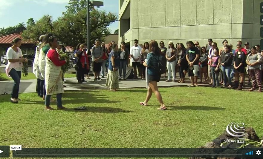 Still from video, students on lawn performing ceremony.