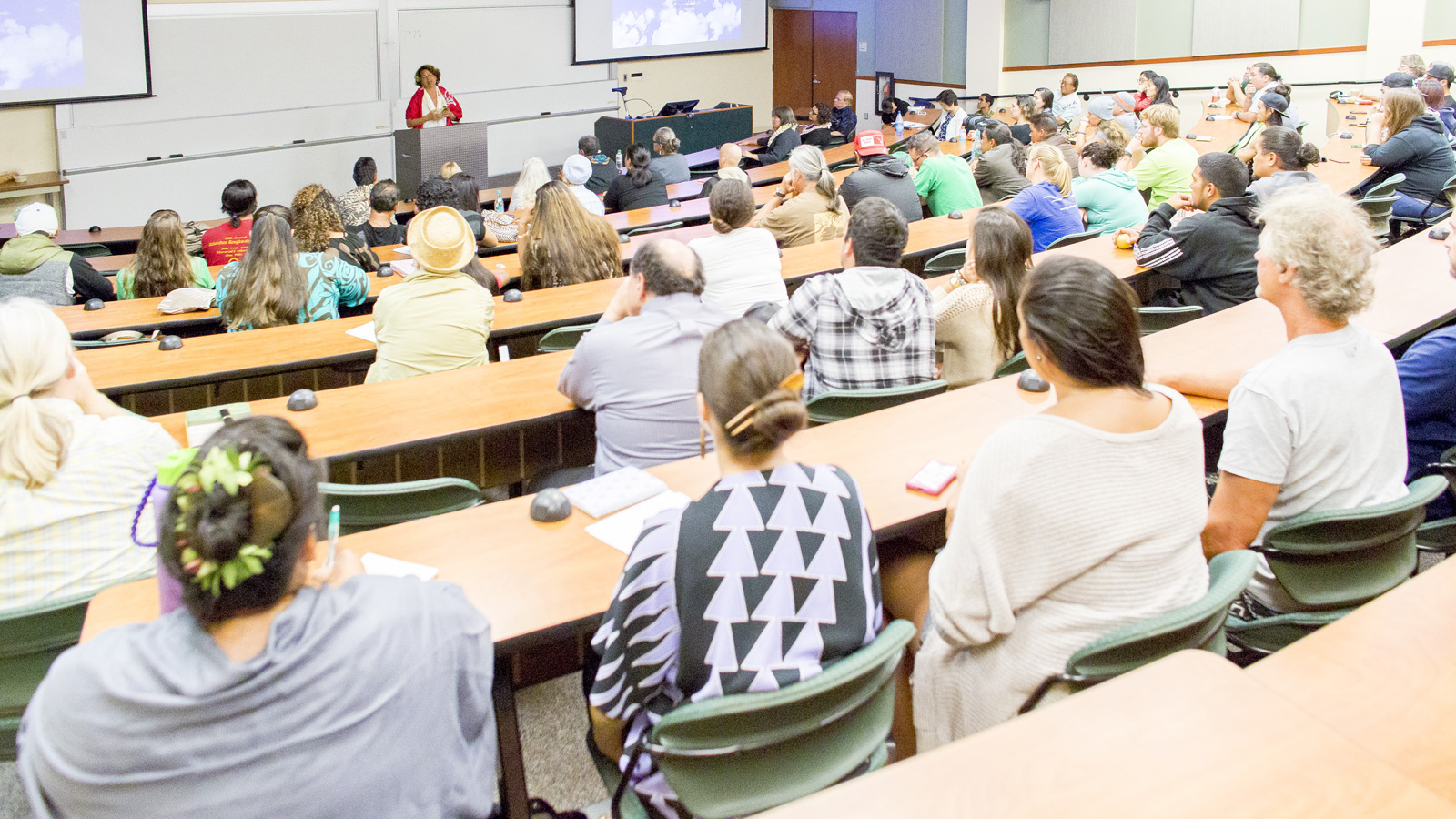 Luana Busby-Neff at podium speaks to audience in lecture hall.