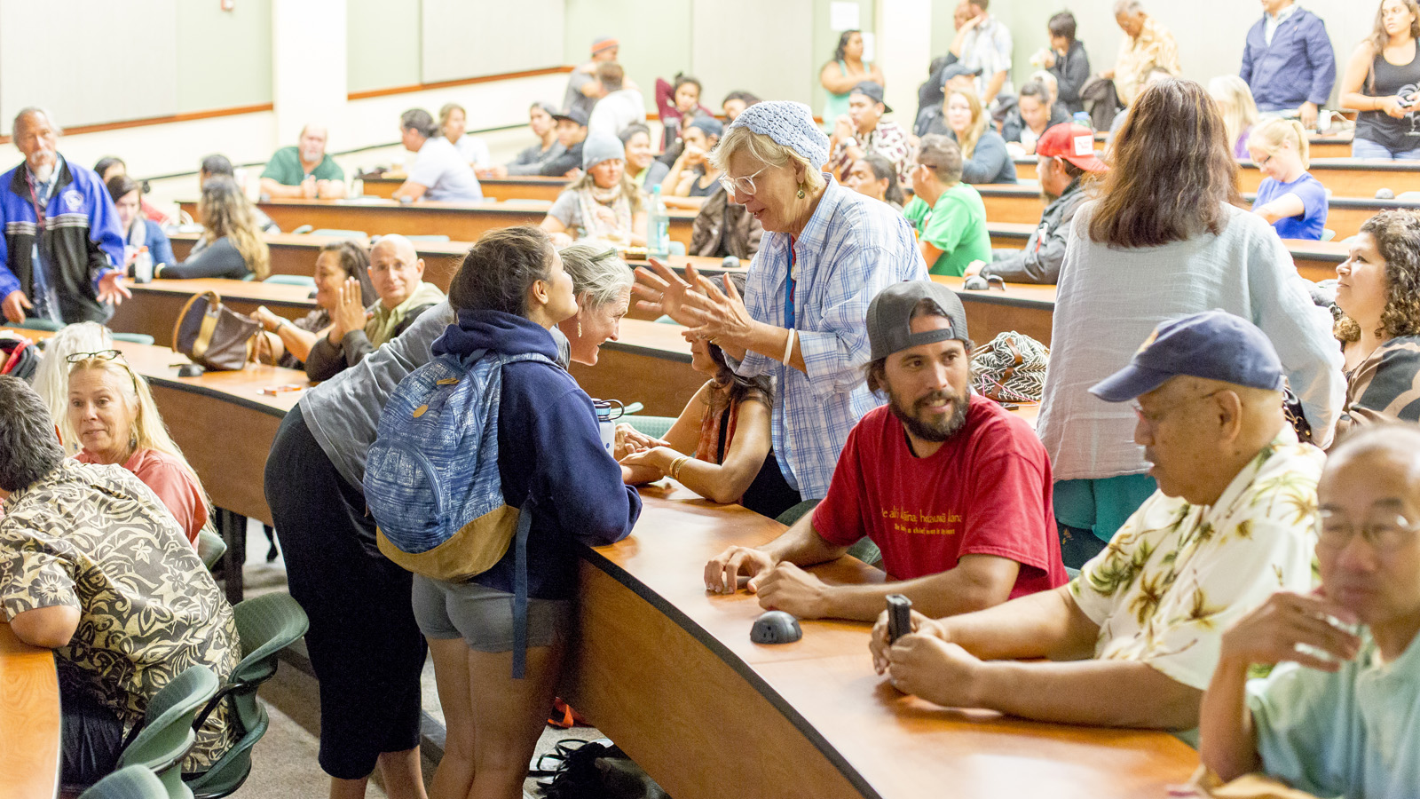Participants engage in breakout discussions in tiered lecture hall.