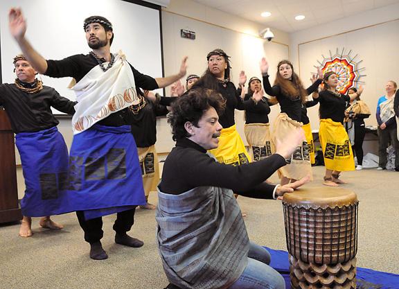 Taupouri Tangaro drumming on pahu with dancers behind him.