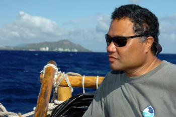 Kalepa Baybayan on board a sailing canoe with Waikiki in the background.