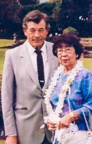 Howard and Yoneko Droste. She wears a lei, he wears a suit and tie. Background is a park.