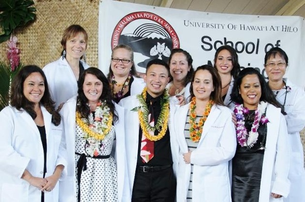 Group photo of 10, all in their white coats, some with lei.