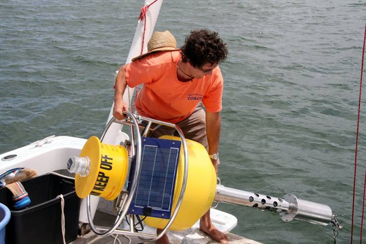 Jason Adolf on boat. launching bouy into water.