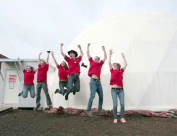 Crew of six in red shirts jumps up in the air with arms held high.