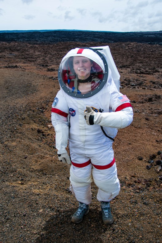 Sophie in white astronaut suit, on cinder terrain, giving thumbs up sign.