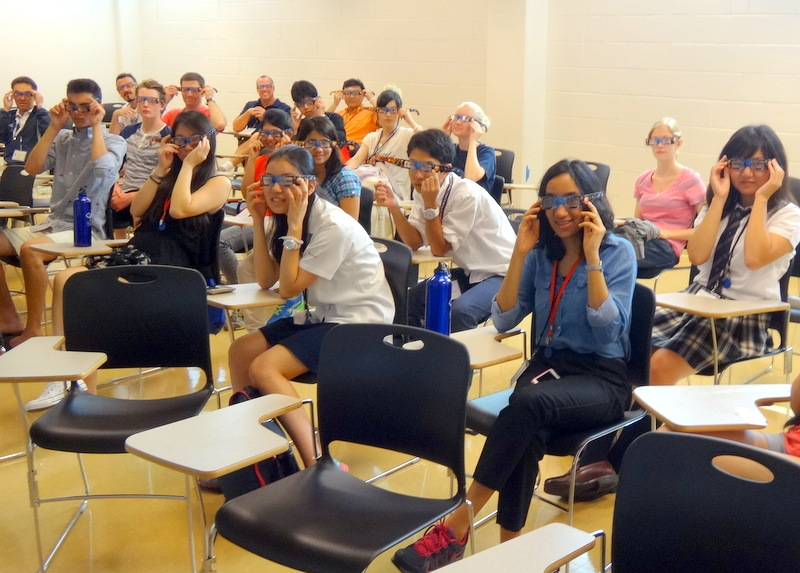 Classroom of students with diffraction glasses on. Most are holding the glasses on.