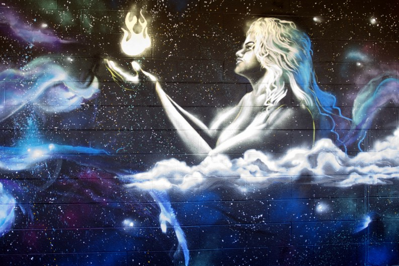 The Hina Wall of the the new Mele Mural at UH Hilo. Hina holds a white flame, and she is surrounded by clouds and stars.