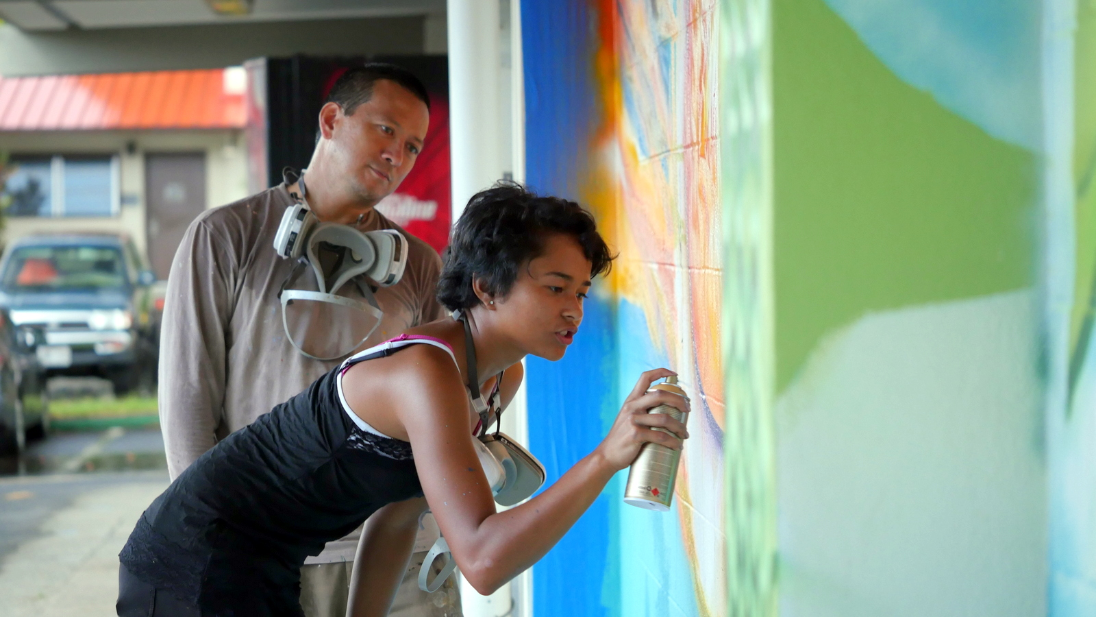 Estria Miyashiro, founder of the statewide Mele Mural project, mentors a student in painting skills.. The student is applying spray paint to the mural.