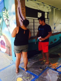 Two students work on mural.