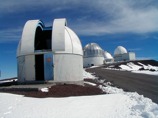 Very small observatory with rounded, open dome. Road to right. Snow on ground.
