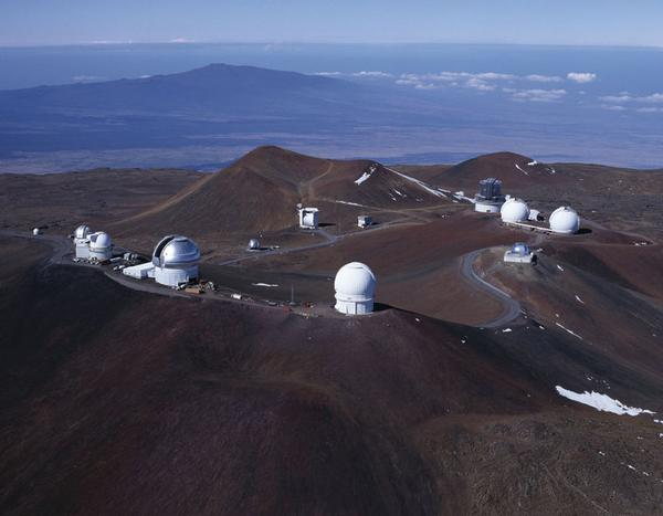 Aerial of summit of Maunakea with several observatories. Small patches of snow.
