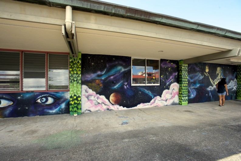 Murals of large eyes, the solar system, and woman holding a flame.